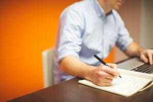 image of a man at his desk taking notes with a pen and notepad.