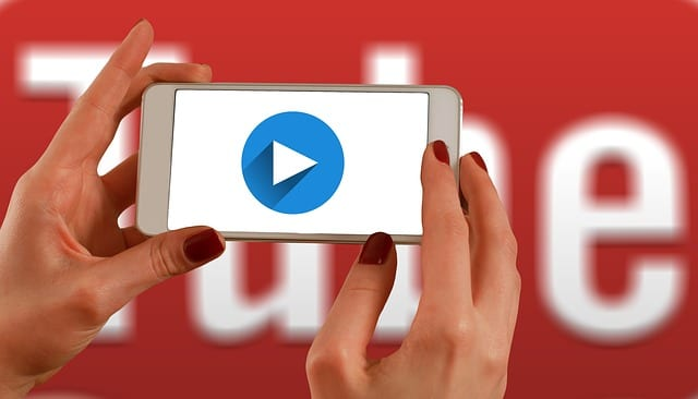 this image shows a cell phone held up by two hands with a play button showing on the screen and the YouTube red logo in the background. Knowing how to embed a youtube video in a website is a great way to improve user experience