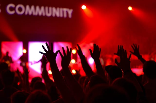how to write a blog for affiliate marketing - image of a crowd of people at a concert holding their hands in the air