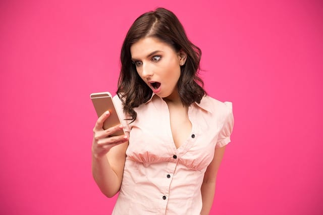 how to write a blog for affiliate marketing - picture of a cute girl staring in awe at what she's reading on her phone